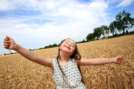 downs syndrome: Young girl have fun in the wheat field Stock Photo