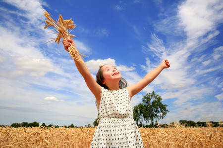 orison: Young girl have fun in the wheat field Stock Photo