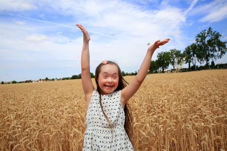 niños discapacitados: Chica joven que se divierte en el campo de trigo