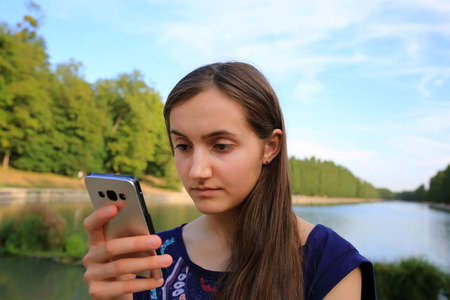 samsung galaxy: Girl with a mobile phone reads the message in the park