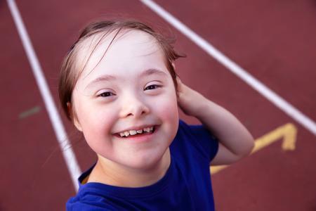 run down: Little girl have fun on the stadium Stock Photo