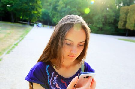 verve: Girl with a mobile phone reads the message in the park