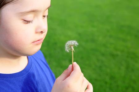 Little girl blowing dandelion 스톡 콘텐츠