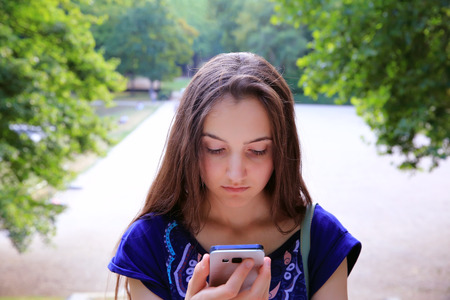 afflatus: Girl with a mobile phone reads the message in the park