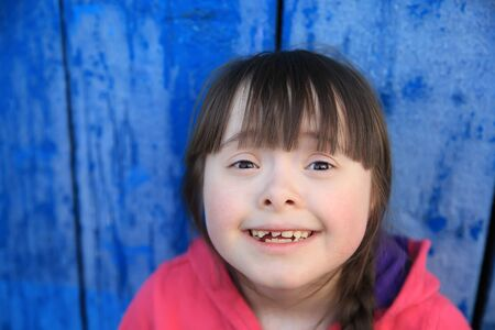 Young girl smiling on background of the blue wall. Imagens