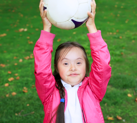 down's syndrome: Cute little girl paying in the park with a ball.