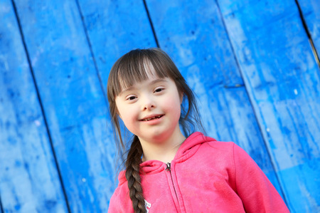 handicap: Young girl smiling on background of the blue wall Stock Photo