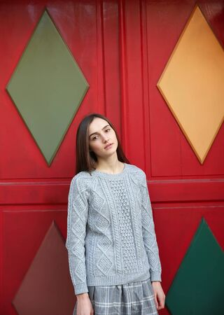 fashion art: Portrait of beautiful girl on background of red door Stock Photo