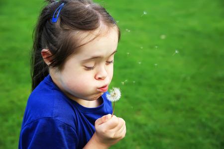 infant school: Little girl blowing dandelion Stock Photo