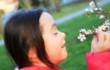 Little girl enjoy with the spring flowers branch Stock Photo