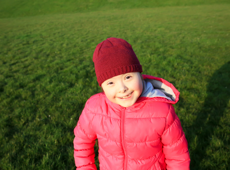 playgroup: Little girl smiling on background of the green grass Stock Photo