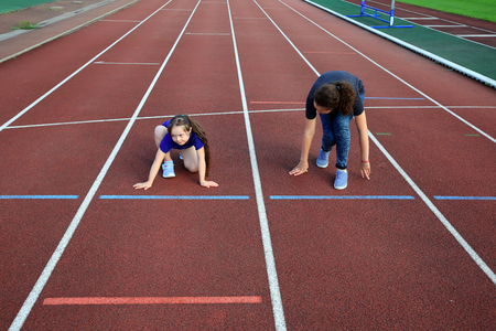 run down: Little girl  with a coach on the stadium