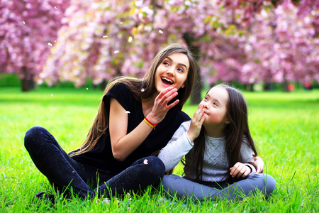 handicap: Happy beautiful young woman with girl in blossom park with trees and flowers.
