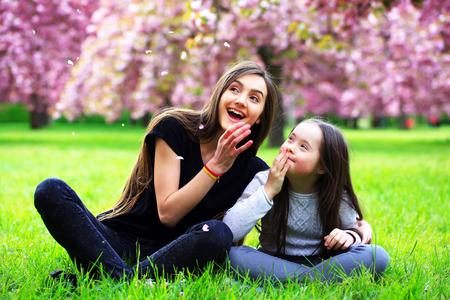 Heureux belle jeune femme avec une fille en fleur parc avec des arbres et des fleurs.