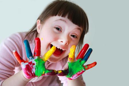 Cute little girl avec les mains peintes. Isolé sur fond gris.