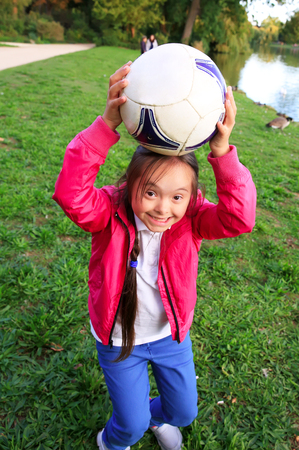 Cute little girl paying in the park with a ball. Stock Photo - 61386612
