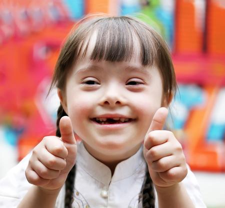 para baixo: Retrato da menina bonita feliz que dá os polegares para cima.