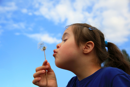 Little girl blowing dandelion Archivio Fotografico