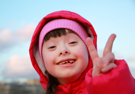 青空の背景に笑っている若い女の子