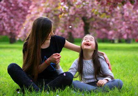 Happy mooie jonge vrouw met meisje in bloei park met bomen en bloemen. Stockfoto
