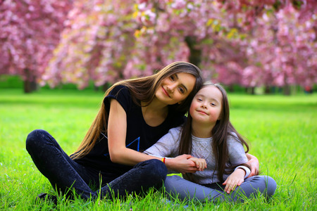 free education: Happy beautiful young woman with girl in blossom park with trees and flowers.