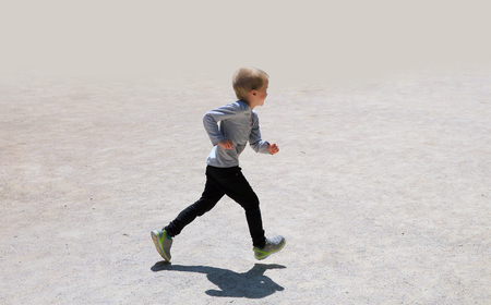 niño corriendo: Little boy running isolated on the grey background