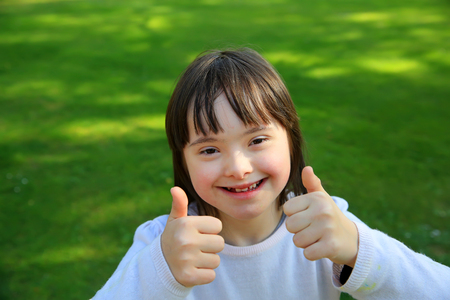 Down syndrome girl smiling in the park