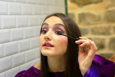Brunette Frau Anwendung Make-up (malen ihre Wimpern) vor einem Spiegel.