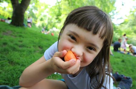 Jeune fille mange l'abricot dans le parc