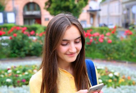 Schönes Mädchen mit Handy liest eine Nachricht in der Stadt.