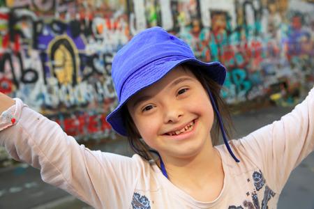 Cute smiling down syndrome girl sur le fond du mur de graffiti Banque d'images - 85526035