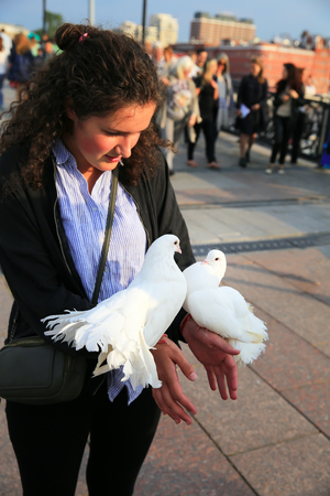 The girl with white pigeons in the city