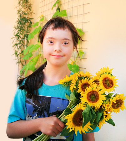 Down syndrome girl with sunflowers Lizenzfreie Bilder