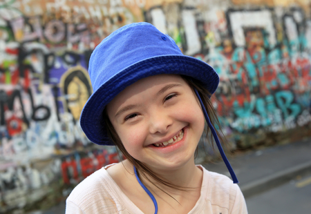 Cute smiling down syndrome girl on the background of the graffiti wall