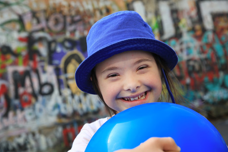 Cute smiling down syndrome girl on the background of the graffiti wall Stock Photo - 85868712
