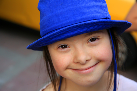 Cute smiling down syndrome girl on the background of taxi