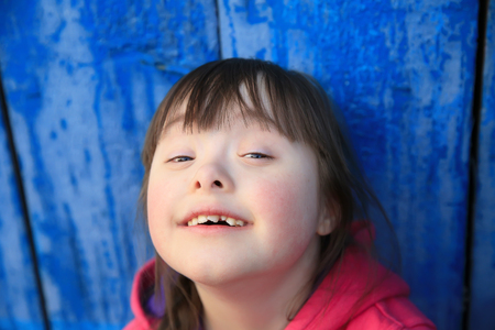 Young girl smiling on background of the blue wall. Lizenzfreie Bilder