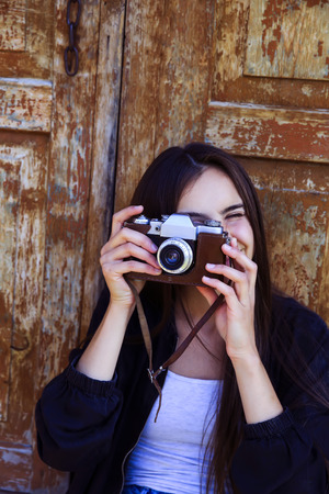 Beautiful girl taking picture with old camera