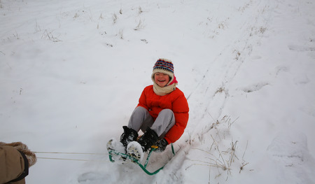 Little girl have fun in the winter with sleigh