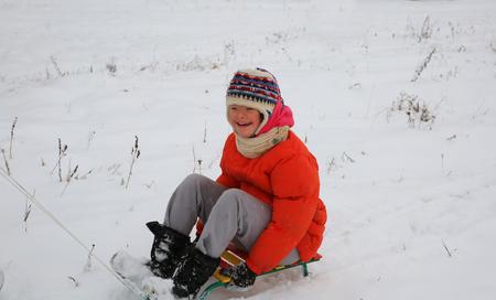 Kleines Mädchen haben Spaß im Winter mit Pferdeschlitten