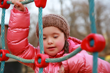 Portrait of down syndrome girl on the playground
