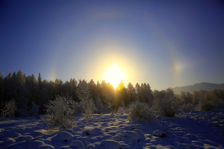 Crystals of frost in air on cold winter day form rare optical phenomenon is rainbow halo around sun. Altai Mountains, Russia Standard-Bild