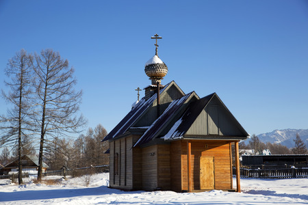 A small church in russian village Zamulta in winter in Uimon Valley, Altai mountains. Standard-Bild
