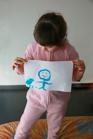 Cute little girl with painting. Isolated on grey background. Standard-Bild