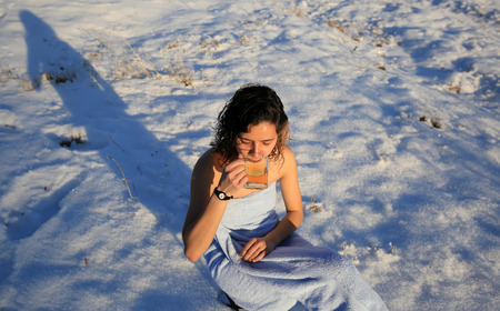 Beautiful girl drinking tea on the snow in winter Standard-Bild