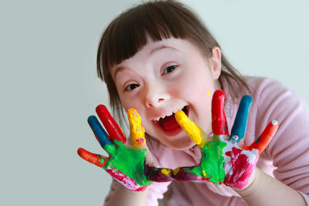Cute little girl with painted hands. Isolated on grey background. Standard-Bild