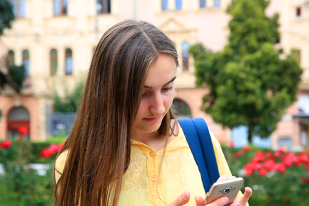 Girl with a mobile phone reads a message