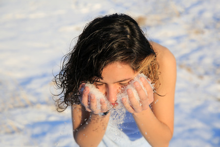 Beautiful girl is washing by the snow in winter Standard-Bild