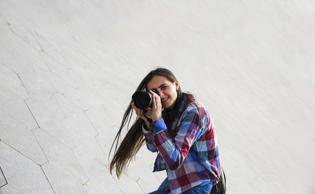Young female photographer on the grey background