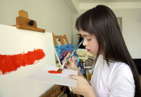 Cute little girl is painting picture